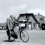 Dorpsomroeper Piet Kliffen op het kerkplein, omstreeks 1950. Op de achtergrond de smederij van Piet Modder, die zelf in de deuropening staat.
