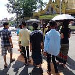 Sonnenschirme gegen die Hitze und Longyis als Alltagskleidung überall