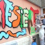 """Das Wort """"Respekt"""" sprühen (von links) Christian, Jan, Samantha und Nina an die Wand ihrer Klassenzimmer-Terrasse."""
