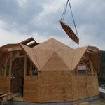 屋根の六角形がクレーンで運ばれます。