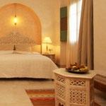 Suite Hawadef:  Au premier étage, fenêtres sur patio et jardin, grand lit, coin salon avec banquette pouvant servir de lit, douche.