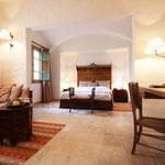 Suite Tombouctou:  Au premier étage, fenêtres sur patio, grand lit, coin salon avec banquette pouvant servir de lit, douche.