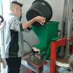Justin füllt die ersten Äpfel in die Maschine.