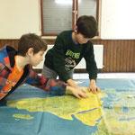Leon und Paul setzen die Spielfigur auf die Landkarte