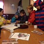 Astrid erklärt den Kindern anhand eines Stofftiers, wie Greifvögel ihr Beute packen