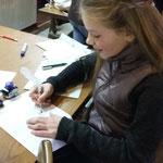 Lana versucht mit einer Feder zu schreiben