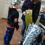 Cara zeigt Alexander wie die Kartons gefaltet werden.