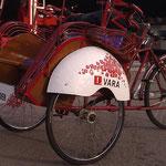 De riksja die door de Vara werd gebruikt met reclame op zowel de wielkasten als op het bord