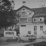 Beladener Lieferwagen vor dem Gasthaus (links) und der Mühle (rechts)