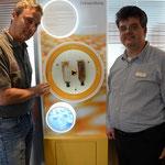 Dirk Ahrens (li.) und Dr. Marco Kollecker vor einer nano-beschichteten Cola-Flasche (li.) – Foto: JPH