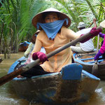 Local woman paddeling through the Mekong Delta