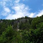 Rechterhand türmen sich spektakuläre Felswände auf