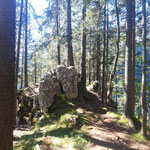 Vorbei an einem Felsen am Wegrand