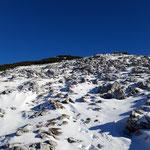 Über Schnee, Felsen und vorbei an der einen oder anderen Doline nähern wir uns dem Gipfel