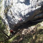 Einen kurzen Abschnitt geht es der Felswand entlang bergab