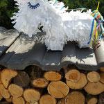 Von einer Lage Buntpapier einen breiten Streifen abschneiden, am Rand zusammenkleben, fransig schneiden und vorsichtig am Kopf befestigen.
