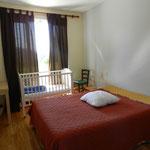 La chambre, son grand lit, et même un lit pour bébé