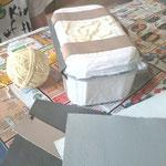 mit dicken Wollfaden ein Truhenmuster ankleben; nochmal eine Schicht Bastelleim und Papierschnipsel auftragen