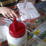 leere Obstbox aus Plastik mit Bastelleim und Papierschnipsel dick bekleben