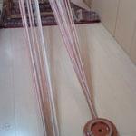 整経した糸を機にかけています。千巻に巻きつけているところ。漬物石が活躍しています。