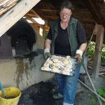 Unsere Backofenmeisterin Birgit Weise mit einem Blech Brötchen, die die Kinder geformt haben und nun auf das Ergebnis warte müssen.