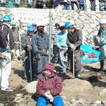 田ノ浦の浜に人が入れないようにするための柵を作るために、作業員がポールを打ち込んでいる。そのポール寄りかかって作業を止めている祝島の女性。(2月21日からの強行工事)