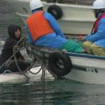 海のフェンスを広げさせないように、作業船にしがみついている祝島の女性。2月の寒い海の中、早朝から午後までしがみついて阻止した。乗っているのは中電。(2月21日からの強行工事)