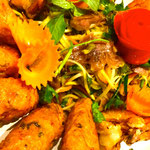 Hausgemachte Tintenfischpaste am Zitronengrasspieß und Rinderwaden-Mango-Salat