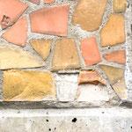 Detailaufnahme von der unteren rechten Ecke des Großmosaiks mit lokalem Verlust von zwei Mosaikplättchen. Aufgrund der beschädigten Mörtelanböschung entlang der Unterkante, ist dieser Schaden offenbar durch Vandalismus entstanden.