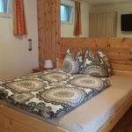 Schlafzimmer mit Zirbenholzwand