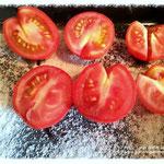 Tomaten auf ein Backblech legen das mit Salz bestreut ist.