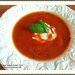 Suppe anrichten mit Basilikumblatt, Sojasahne und Ingwerstückchen.