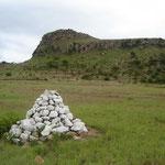 Il monte Isandlwana ripreso nel 2005; il cumulo di pietre bianche indica la collocazione di una delle fosse comuni dove furono seppelliti i caduti britannici.