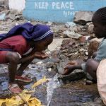 Bambini di Kibera bevono in un canale di scolo.