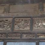 zeigt uns die alten Holzverzierungen über der Türe