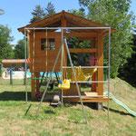 La cabane de jeux avec bac à sable, toboggan, hamac et balançoires