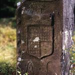 Der Grenzwappenstein in der Hängeleite bei Buchbach mit dem schwarz-weißen Hohenzollern-Wappen ist ungewöhlicherweise als Segment gehauen. Die Initialen A.L. bedeuten Amt Lauenstein, das zur Markgrafschaft Ansbach-Bayreuth gehörte.