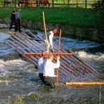 Im eiskalten Wasser wird versucht, das Floß wieder flott zu machen.