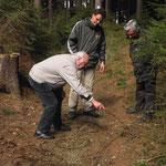 In einem Hohlweg erklärt Georg Heinlein anhand einer Boden-Skizze, wie mit alten Fuhrwerken mit Ketten und Hemmschuhen gebremst wurde und der Weg sich deshalb nach und nach eingetieft hat.