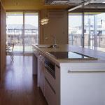 厨房の後ろの壁が全て収納となって、すっきりした室内を実現している。