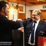 Jugendwart Sebastian Bertelmann übergibt seinem Vorgänger OLM Karl-Wilhelm Lehmann ein Präsent der Jugendfeuerwehr