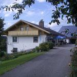 Blick von der Zufahrt auf das Haus und den Garten