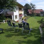Blick vom Rasen oben auf die Terrasse und Liegewiese, über dei Relax-Bäderliegen