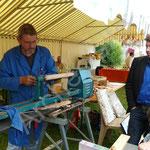 Jean-Patrick réalise quelques toupies antiques au tour à bois.