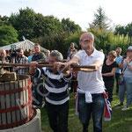 Deux visiteurs poussent la barre qui va entraîner le pressurage du raisin.