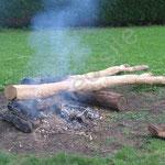 Les poteaux sont transportés vers un brasier afin de brûler l'extrémité.
