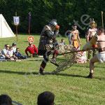 L'homoplaque, avec sa lance, met en difficulté le rétiaire et son filet sous le regard attentif de l'arbitre.