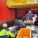 Aufnehmen des Ölfilms mit Fleecetüchern, teils unter den vertäuten Schiffen © FF-Duhnen
