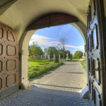 Blick durch das Tor der Pforte in Richtung der Gartenanlage