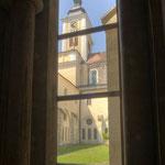 Blick aus dem Kreuzgang über den Garten auf die Kirche